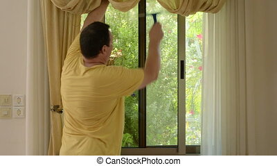 Man cleaning a window - Mature man cleaning a window at home