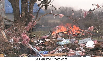 Tornado Wreckage With Fire 1 - A large fire burns in the...