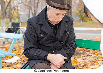 Depressed lonely old man sitting in his overcoat on a park...