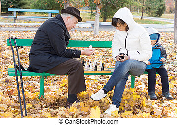 Attractive woman playing chess with her father as they sit...