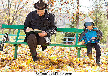 Grandfather and grandson reading in the sun - Grandfather...