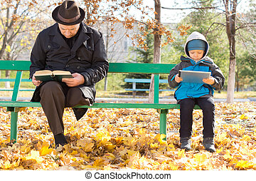 Elderly man and small boy sharing a park bench - Elderly man...