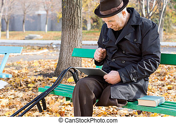 Elderly disabled man reading an e-book - Elderly one legged...