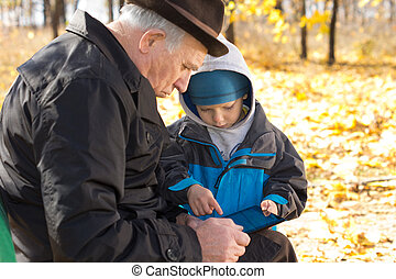 Grandfather and grandson sharing a tablet-pc - Grandfather...