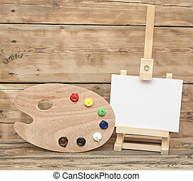 Wooden easel with clean paper and artist color palette