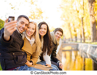 group of friends with photo camera in autumn park - summer,...
