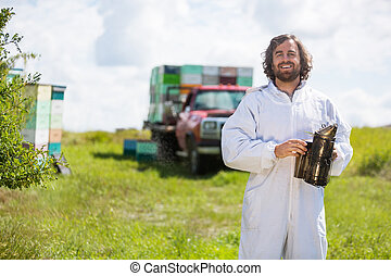 Beekeeper In Holding Smoker At Apiary - Portrait of happy...