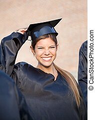 Woman In Graduation Gown Holding Mortar Board On Campus -...