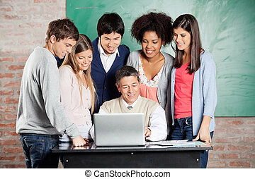 Professor And Students Looking At Laptop In Classroom -...