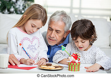 Grandfather assisting children in writing letters to Santa...