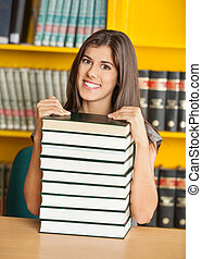 Beautiful Woman With Piled Books Smiling In Library