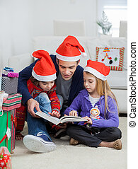 Father And Children In Santa Hats Reading Book - Full length...