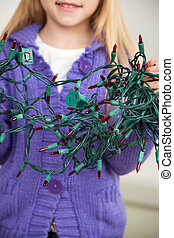 Girl Holding Tangled Fairy Lights - Midsection of girl...