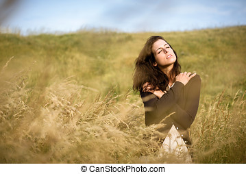 Sadness and nostalgia in nature - Sad shivery woman in brown...