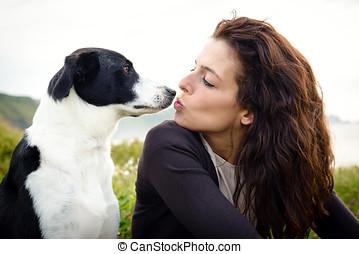Dog and woman kiss