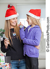 Mother And Daughter Decorating Christmas Tree - Smiling...