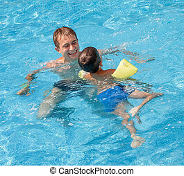 Father teaching his son to swim in the pool