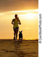 Woman and dog running on sunset - Woman and dog running...