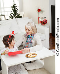 Woman Assisting Boy In Making Christmas Greeting Card