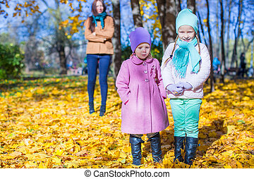 Two adorable girls with his young mom in the park on a sunny autumn day