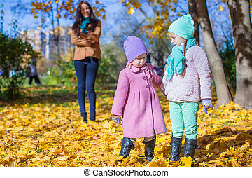 Two beautiful adorable daughter walking with his young mom in the park on a sunny autumn day