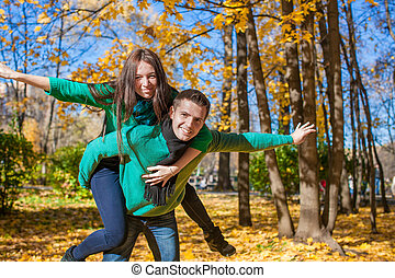 Happy couple having fun in autumn park on a sunny fall day