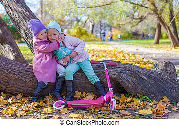 Little beautiful girl with scooter in the autumn park