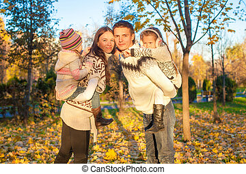 Family of four having fun in autumn park on a sunny warm day