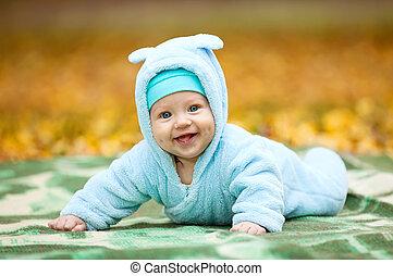 Happy baby boy in autumn park