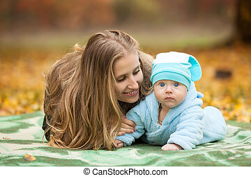 Woman with baby in autumn park