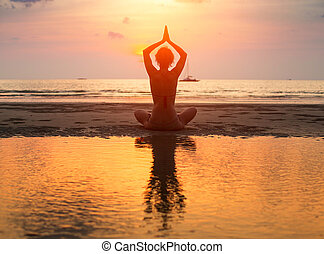 Yoga woman sitting in lotus pose on the beach during sunset with reflection in water.