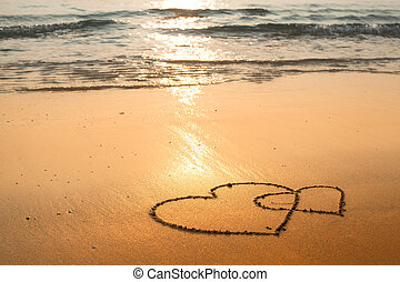 Hearts drawn on the sand of the sea beach.