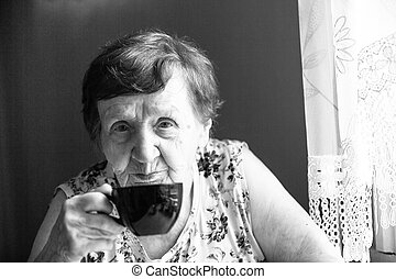 Portrait an old woman is drinking tea, black and white.