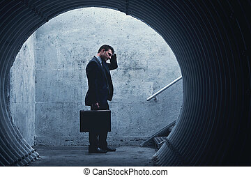 Desparate Businessman Holding his head in a dark tunnel. -...