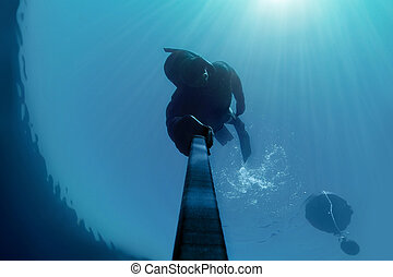 Freediver holding his breath deap in the water with Sunlight...