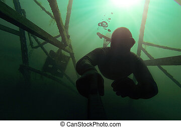 Freediver going deap in the water with a structure above him...