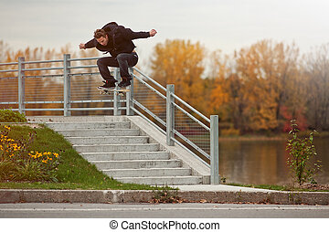 Skateboarder doing a Ollie down the stairs - Young...