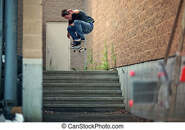 Skateboarder doing a Kickflip down the stairs - Young...