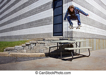 Young Skateboarder doing a Ollie trick over a Picnic Table