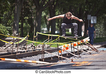 Skateboarder doing a Ollie trick over construction - Young...