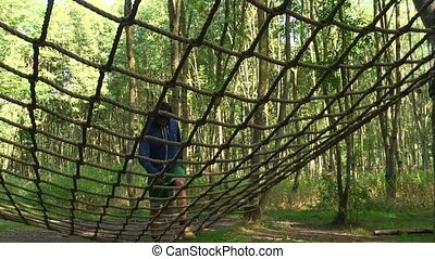 Assault Course - Young man climbing over a net on an assault...
