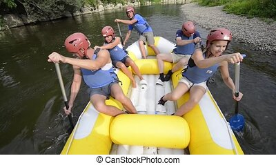 Rafting - Five people rowing on a river in a white water...