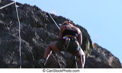 Abseiling Woman - Young woman, abseiling from an almost...