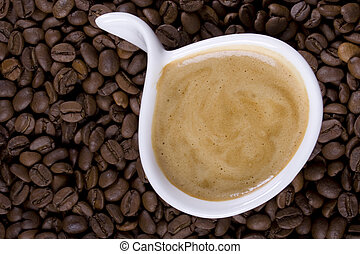 Creamy coffee - Cup of creamy espresso on coffee beans
