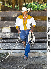 Mexican Cowboy - A cowboy leaning on a fence with a lariat