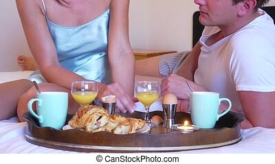 Couple with a breakfast in bed - Pan up from a wooden tray...