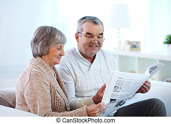 Reading couple - Portrait of mature couple reading newspaper...
