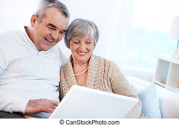 Home internet - Portrait of mature man and his wife working...