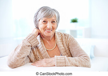 Aged woman - Portrait of aged female looking at camera with...
