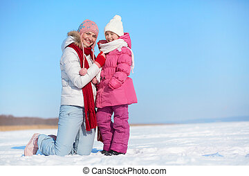 Affection - Happy woman and her daughter in winter wear...
